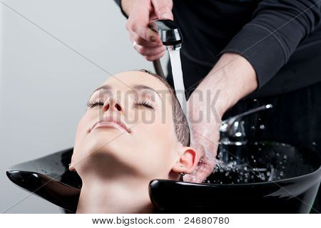 Young Woman Getting Her Hair Washed At The Hairdresser. Close Up.
