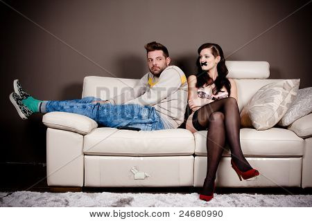 A Bizarre Living Room Scene. A Woman In Lingerie With Her Mouth Taped And A Hunched Weird Man On The