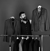 Official Wardrobe Choice Concept. Man With Beard By Clothes Rack. Businessman With Happy Face Holds  poster