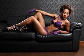 stock photo of sulky  - Sexy body of beautiful young african american glamour model woman wearing purple lace lingerie and leather gloves lying on black leather sofa with killer stiletto heels - JPG