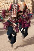 image of dogon  - Mali, December 30, 2009: Mask dances at Dogon funeral rites near Bandiagara Escarpment. The Dogon are best known for their mythology their mask dances wooden sculpture and their architecture. - JPG
