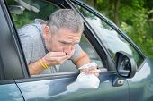 Man suffering from motion sickness in a car and holding sick bag poster