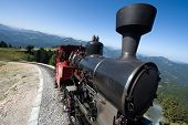 image of railcar  - An old steam locomotive is climbing up the  - JPG