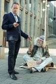 Rich And Poor. Elderly Rich Successful Businessman Feeling Helpful While Giving Some Money To Poor M poster