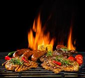 Delicious pieces of meat on grill with Fire flames. Isolated on black background. Barbecue and grill poster