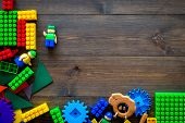 Educational Children Toys Mockup. Plastic Lego Blocks And Clacks On Dark Wooden Background Top View. poster