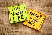 live your life, forget your age - inspirational handwriting on sticky notes against burlap canvas poster