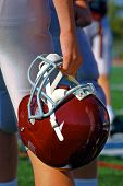 picture of football helmet  - A football player holds his helmet while watching from the sideline - JPG