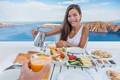 Couple eating breakfast at luxury resort - honeymoon Europe travel vacation, Santorini, Greece. Asia poster