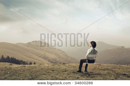 Businessman sitting on a chair and observing the panorama