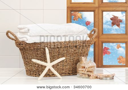 Basket of washing with raindrops on window and falling autumn leaves
