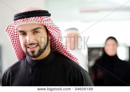 Confident young Saudi business executive with his team in the background