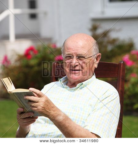 Happy Pensioner Relaxing With A Book