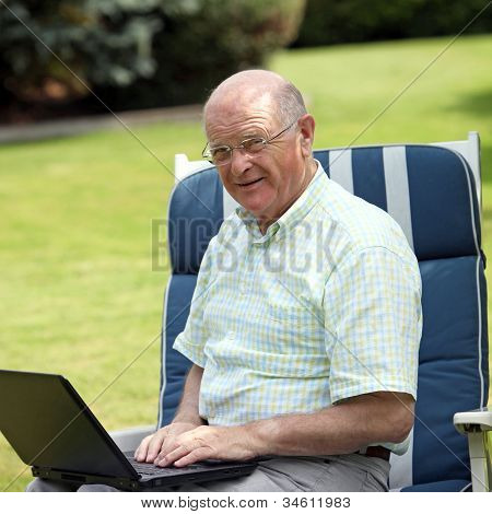 Senior Man Typing On A Laptop