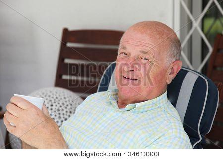 Elderly Man Enjoying A Cup Of Tea