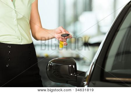 Woman standing with key next to her new bought or rental car