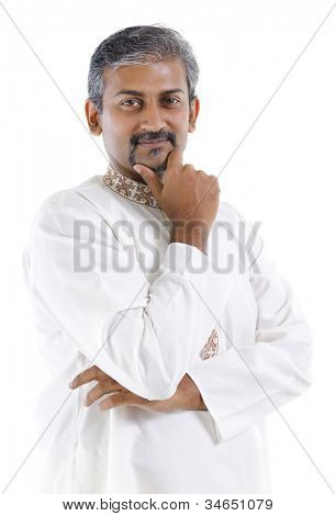 Confident mature traditional Indian man in kurta dhoti isolated on white background