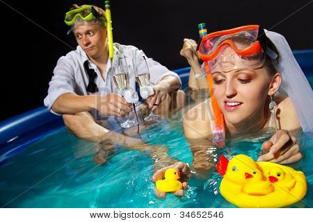 A young beautiful bride is enjoying in pool with mask and snorkel and her groom waiting for her with glasses of champagne
