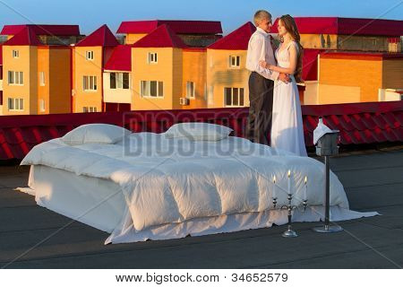 Wedding shot of bride and groom next to a stylish bed on roof in the morning