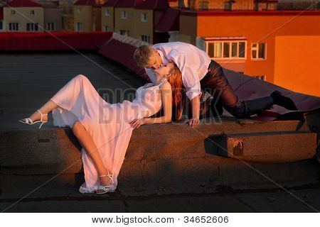 The newly married couple lying on the roof of house in red sunset