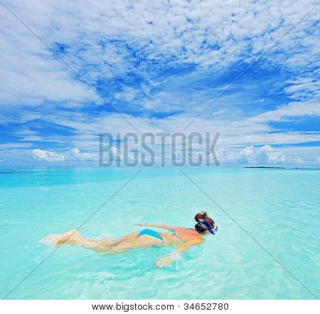 A woman with snorkeling mask diving in Kuredu resort, Maldives island, Lhaviyani atoll