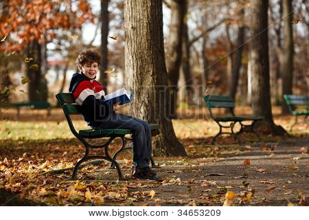 Boy reading book sitting in park