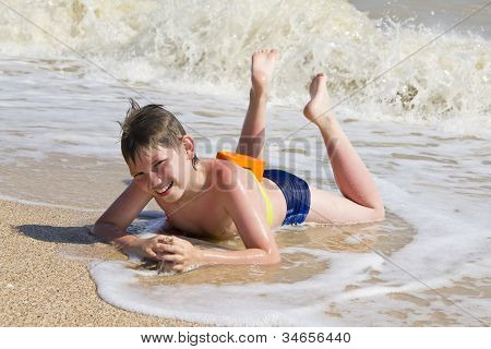Boy Lying On The Beach In The Surf