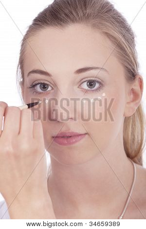 Young Beautiful Woman Applying Concealer On Face