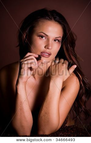 Sexy young woman in coffee beans with beautiful brown make-up
