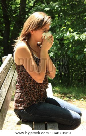 Woman in the park blowing her nose