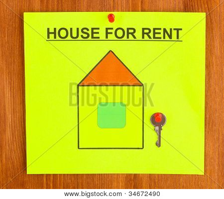 poster about renting the house with the key on wooden background close-up