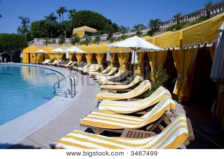 Pool With Yellow Cabanas And Striped Towels