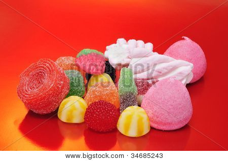 a pile of tasty candies on a red background