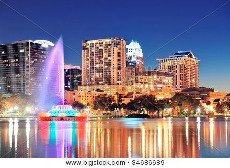 Orlando downtown skyline panorama over Lake Eola at night with urban skyscrapers, fountain and clear sky.