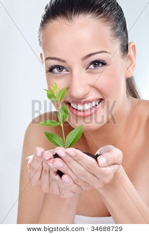 Beautiful girl holding young plant in her hand
