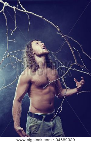 Screaming athletic man in forest, with fog on background