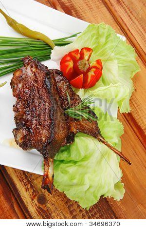 Fleisch-Platte über Holztisch: gegrillte Rippen auf weißen Teller mit roten Peperoni, Tomaten und Schnittlauch