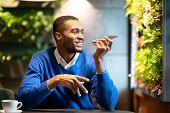 Voice Search. Happy Black Man Using Voice Assistant On Mobile Phone Or Calling On Smartphone At Cafe poster
