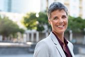 Portrait of senior businesswoman standing outdoor and looking at camera. Successful mature stylish w poster