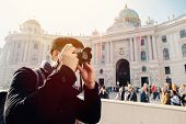 Young Asian Man Tourist Taking Photos With Camera In Hands Near Hofburg Palace In Vienna, Austria, E poster