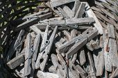Pile Of Weathered Wooden Laundry Clamps Closeup In Reed Basket poster