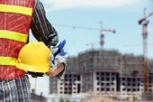 stock photo of personal safety  - man holding yellow helmet in front of construction site - JPG