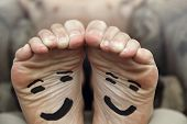 stock photo of sole  - Funny image of a pair of bare male feet with happy smiley face drawn on bottom - JPG