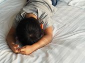 Little Asian Boy Feel Boring On Bed. Depressed Little Boy Lying Face Down On The Bed In Sad Moody. S poster