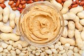 Creamy Peanut Paste, Peanut Butter In Open Glass Jar In The Center Of Peanuts Food Background. Peanu poster