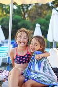 Two Cute Little Girls Hugging And Smiling At The Seaside At Sunset.  Summer Sunny Day, Ocean Coast,  poster