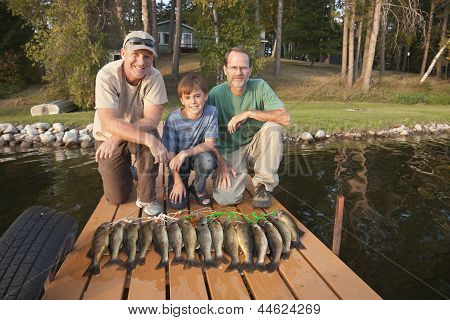 Two Men And A Boy Posing With Catch Of Fish