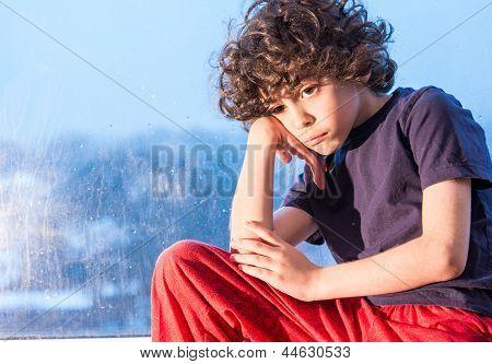 Sad Child Sitting On A Window On A Rainy Day