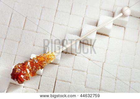 candy brown sugar on a stick lies on lumpy sugar