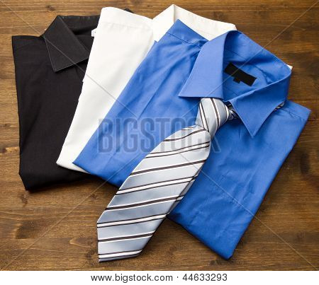 Close Up Of Stacked Shirts With Tie.